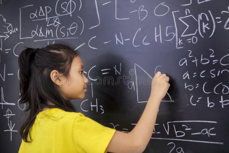La studentessa scrive la formula di matematica immagine stock