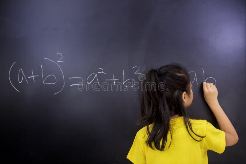 La studentessa scrive le equazioni matematiche fotografia stock