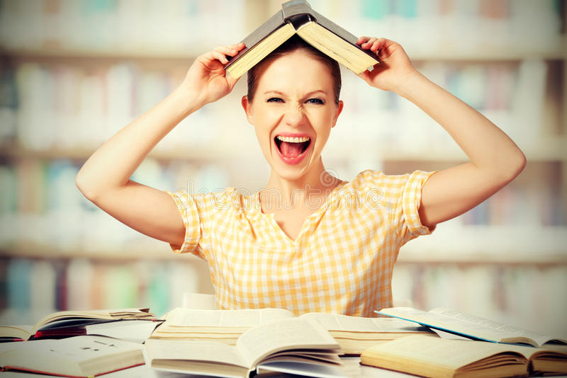 La studentessa selvaggia con i vetri grida con i libri fotografie stock