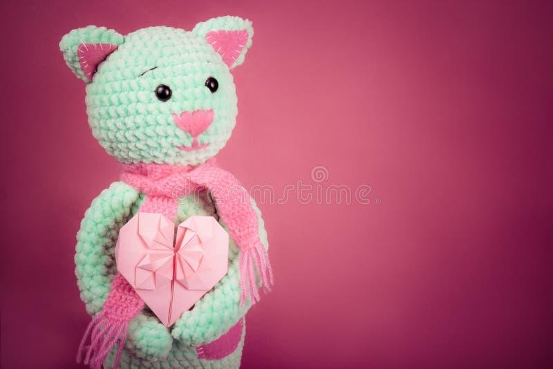 La suavidad hizo punto la tarjeta del gato y de la tarjeta del día de San Valentín en fondo rosado Juguete hecho punto suavidad R fotos de archivo
