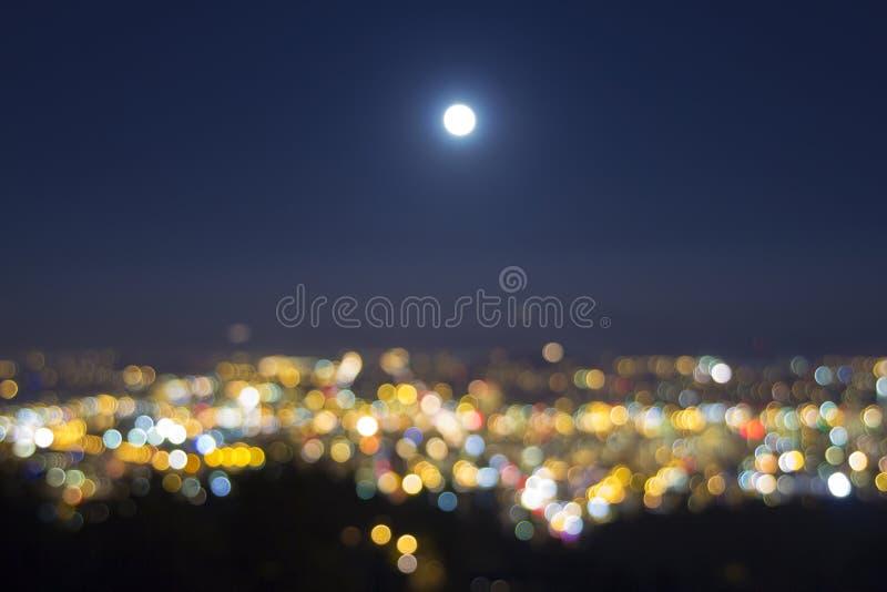 La subida de la Luna Llena sobre ciudad borrosa enciende paisaje fotos de archivo