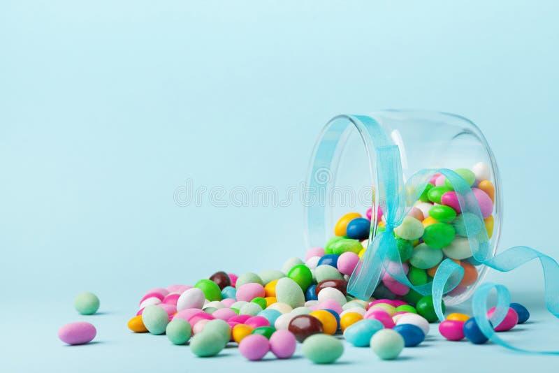La sucrerie colorée sont dispersées sur le fond bleu Cadeaux pour l'anniversaire ou les Joyeuses Pâques photographie stock libre de droits