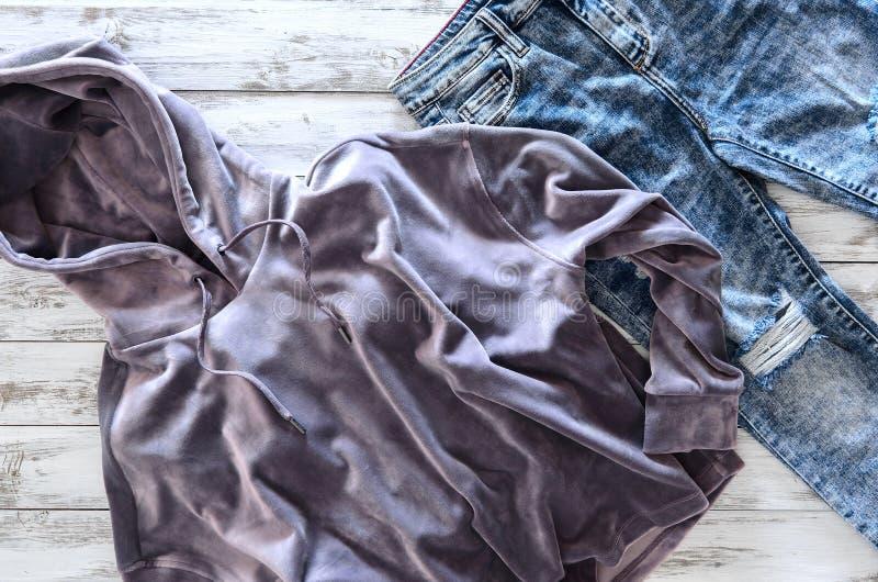 La sudadera con capucha violeta del terciopelo de la ropa para mujer, ácido lavó vaqueros encendido corteja fotografía de archivo