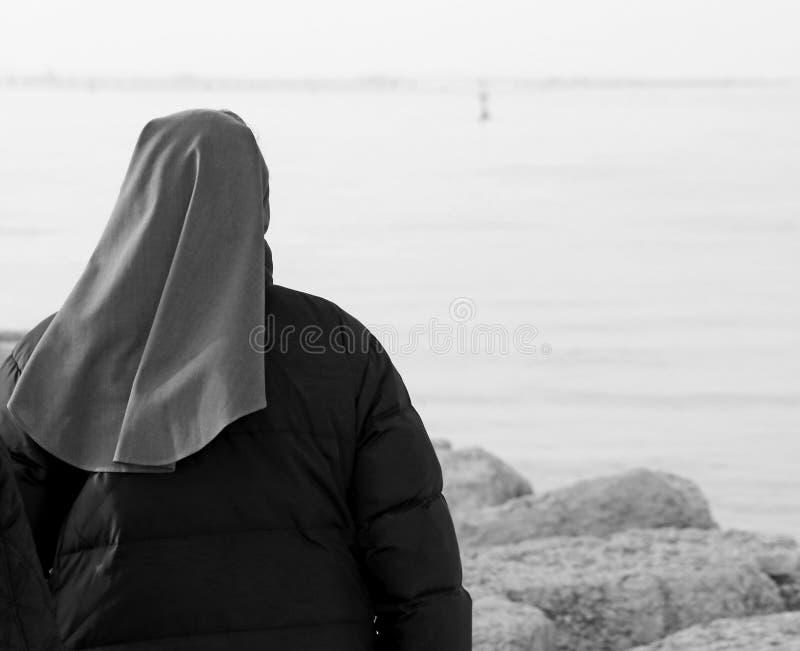 La suora cammina nell'inverno vicino all'oceano fotografia stock libera da diritti