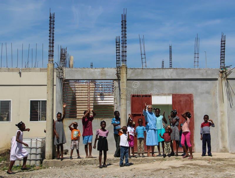 La suora e gli orfani ondeggiano ai missionari in Normale-du-Nord, Haiti fotografia stock libera da diritti