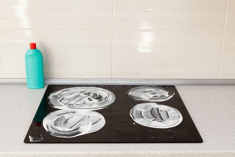 La superficie de la estufa de la inducción se cubre con un detergente Limpieza de la casa - botellas plásticas con los detergente fotografía de archivo