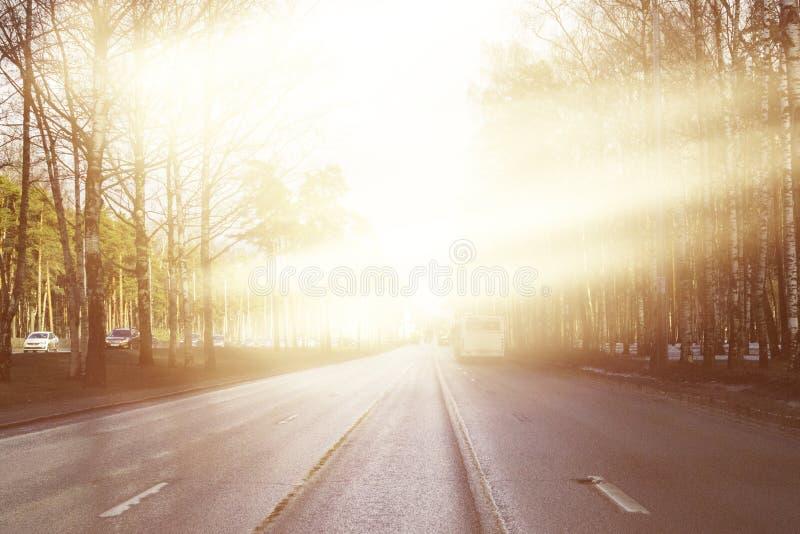 La superficie del camino es iluminada por los rayos del sol Pista lisa larga en el camino asfalto borrado fotos de archivo