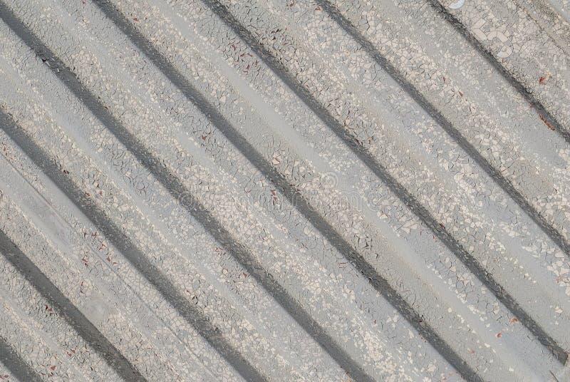 La superficie del hierro acanalado se cubre con la pintura vieja, pintura saltada, textura gris, fondo foto de archivo