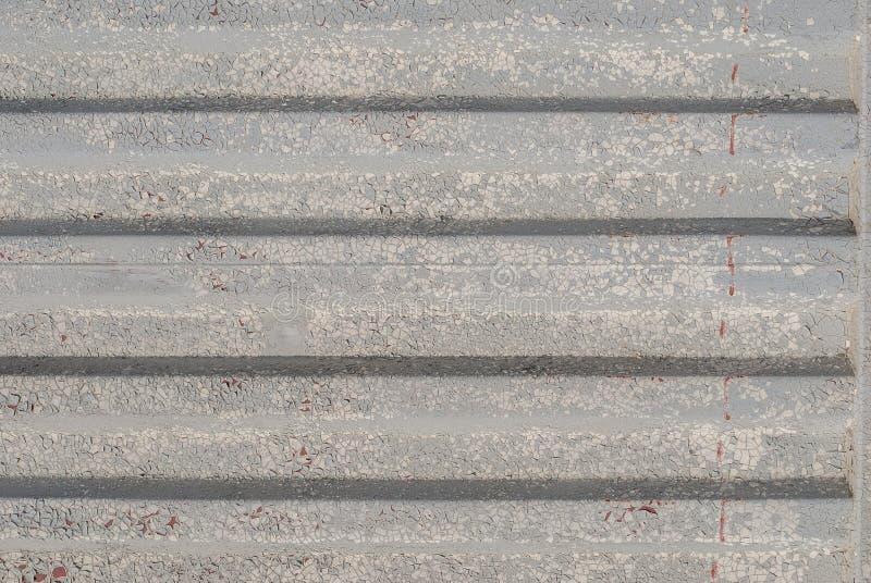 La superficie del hierro acanalado se cubre con la pintura vieja, pintura saltada, textura gris, fondo imagen de archivo libre de regalías