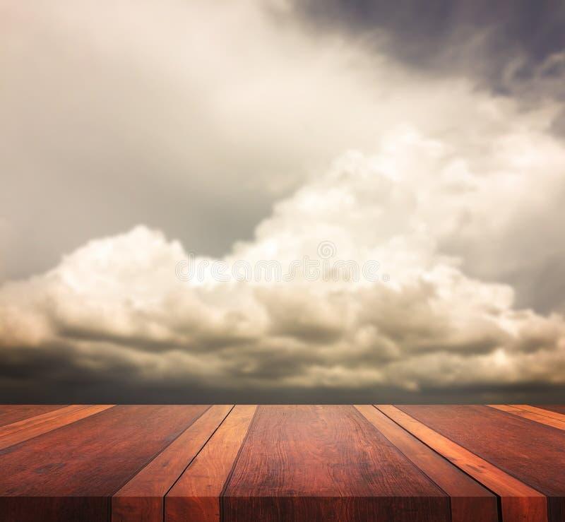 La superficie di legno marrone vuota della tavola e l'immagine di sfondo vaga cielo, per il montaggio dell'esposizione del prodot fotografia stock