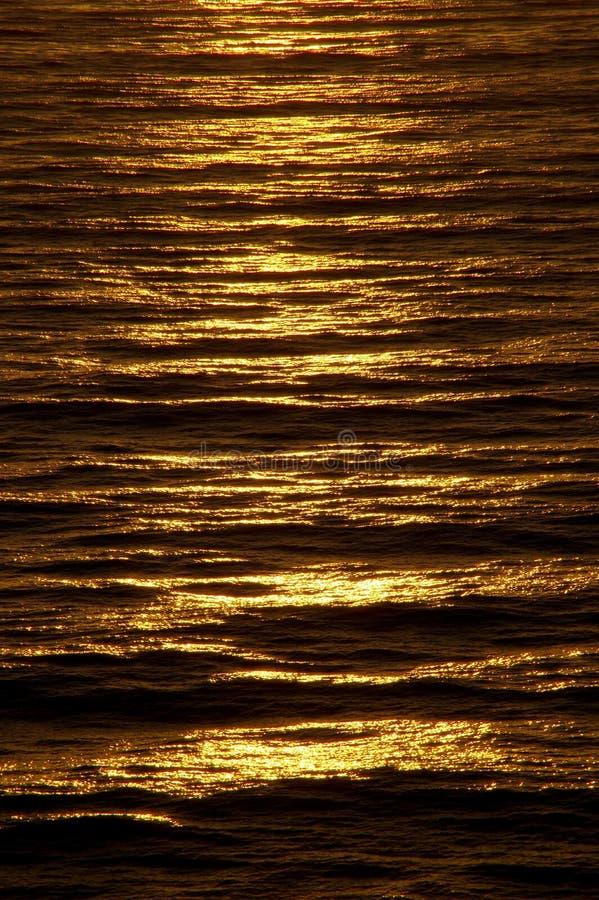 La superficie ondulada del océano brilla intensamente con color de cobre rico en el ocaso fotografía de archivo