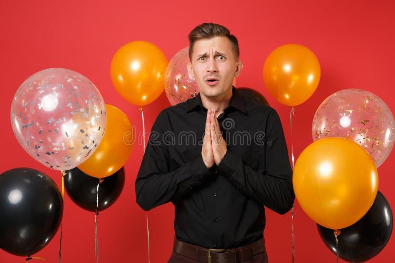 La supplica del giovane in camicia classica nera ha piegato le sue mani e pregare sugli aerostati rossi del fondo ` S del bigliet fotografia stock libera da diritti