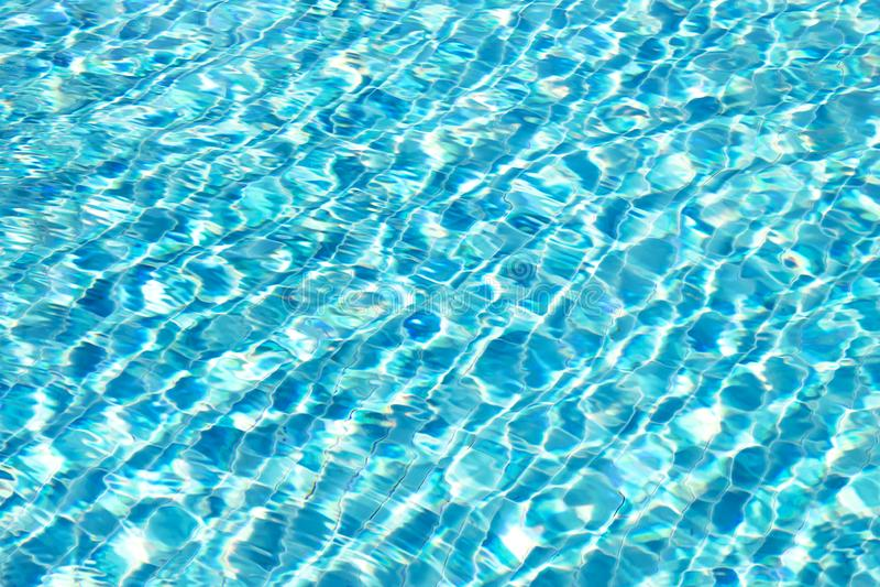 La surface de l'eau de la piscine se reflète dans la lumière du soleil images stock