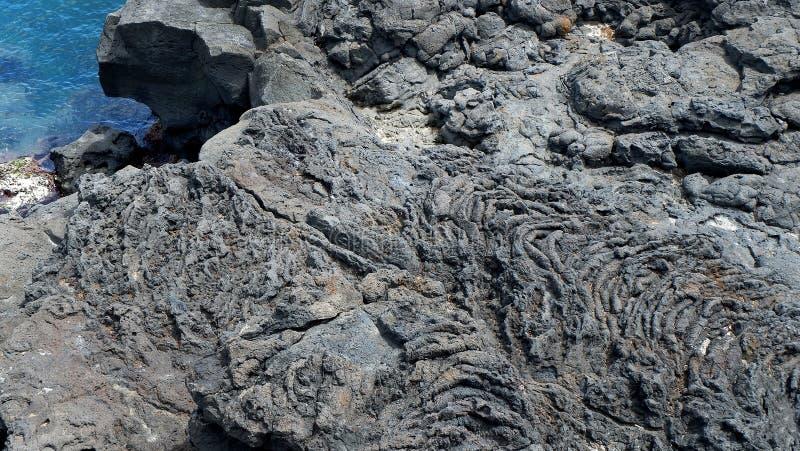 La surface de la pierre volcanique Noircissez le fond en pierre Oscillez la texture Fond de pile de roche image libre de droits