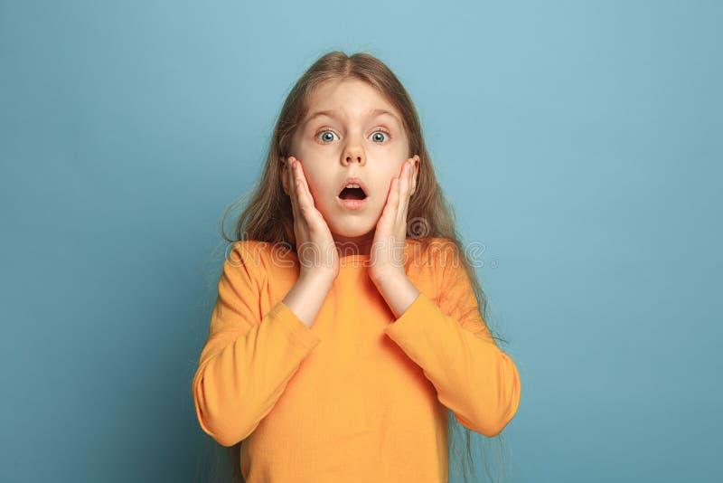 La surprise, le bonheur, la joie, la victoire, le succès et la chance Fille de l'adolescence sur un fond bleu Expressions du visa photo stock