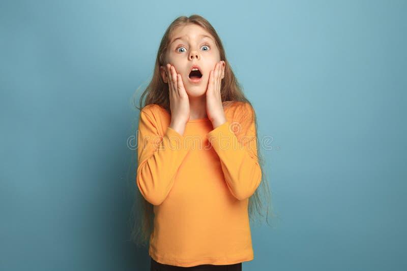 La surprise, le bonheur, la joie, la victoire, le succès et la chance Fille de l'adolescence sur un fond bleu Expressions du visa image libre de droits