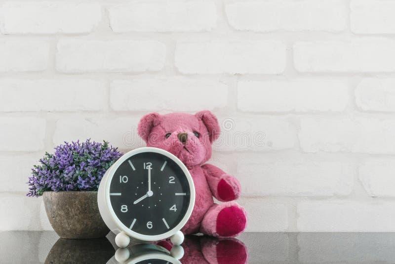 La sveglia in bianco e nero del primo piano per decora in orologio del ` di 8 o con la bambola e la pianta dell'orso sulla tavola fotografia stock libera da diritti
