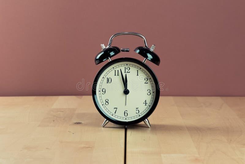 La sveglia d'annata sta mostrando il movimento di mezzanotte o di mezzogiorno i immagini stock libere da diritti