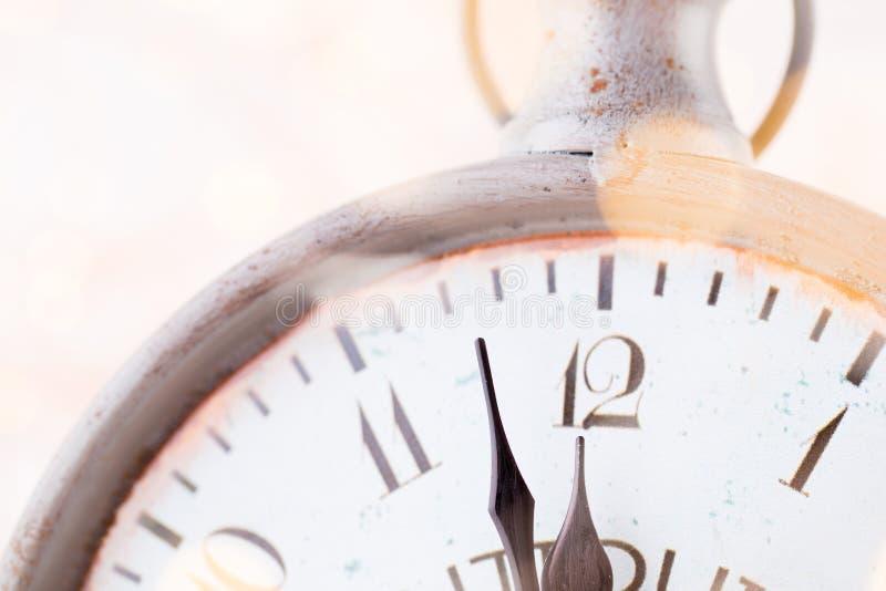 La sveglia d'annata sta mostrando la mezzanotte ? dodici in punto, natale e bokeh, concetto festivo del buon anno di festa sopra fotografia stock