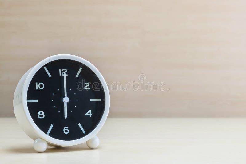 La sveglia del primo piano per decora nell'orologio del ` di 6 o sullo scrittorio di legno marrone e nel fondo strutturato parete fotografie stock