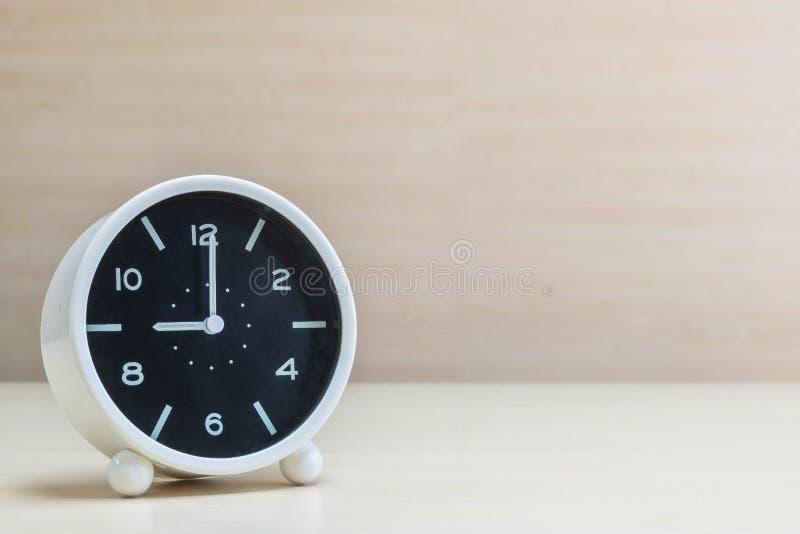 La sveglia del primo piano per decora nell'orologio del ` di 9 o sullo scrittorio di legno marrone e nel fondo strutturato parete fotografie stock libere da diritti