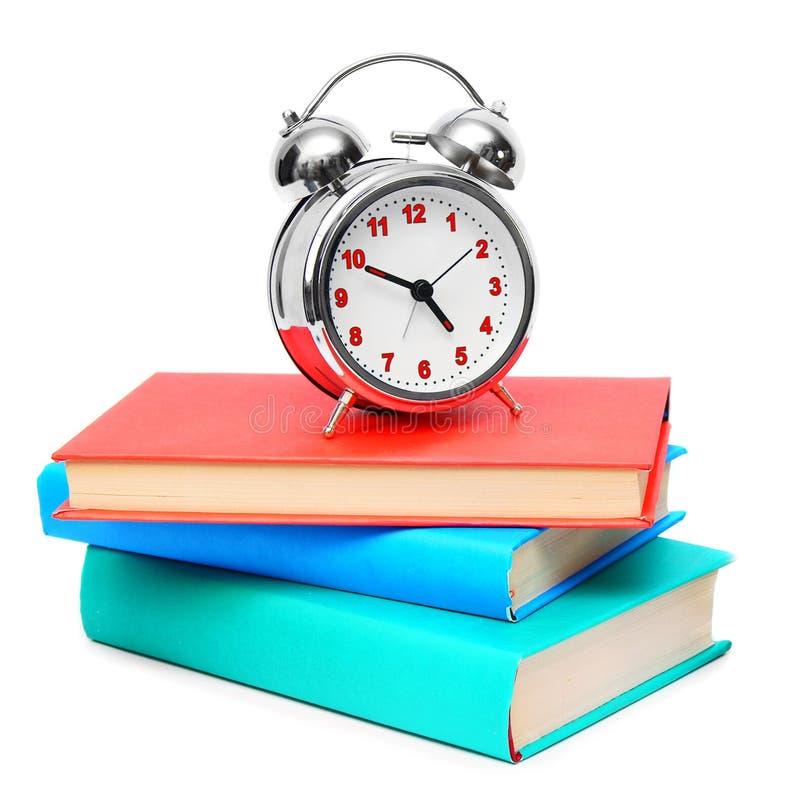 La sveglia ed i libri. immagine stock