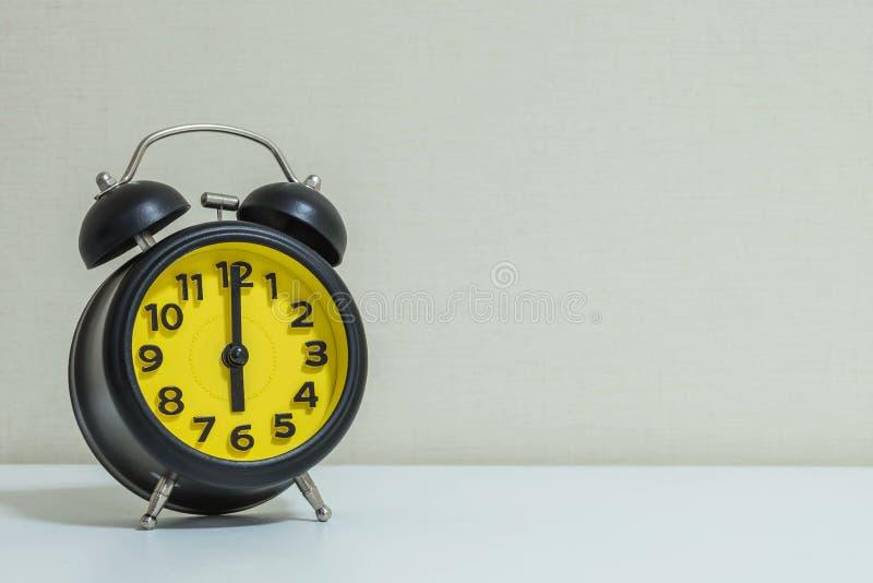 La sveglia gialla e nera del primo piano per decora in orologio del ` di 6 o sul fondo strutturato carta da parati di legno bianc immagini stock