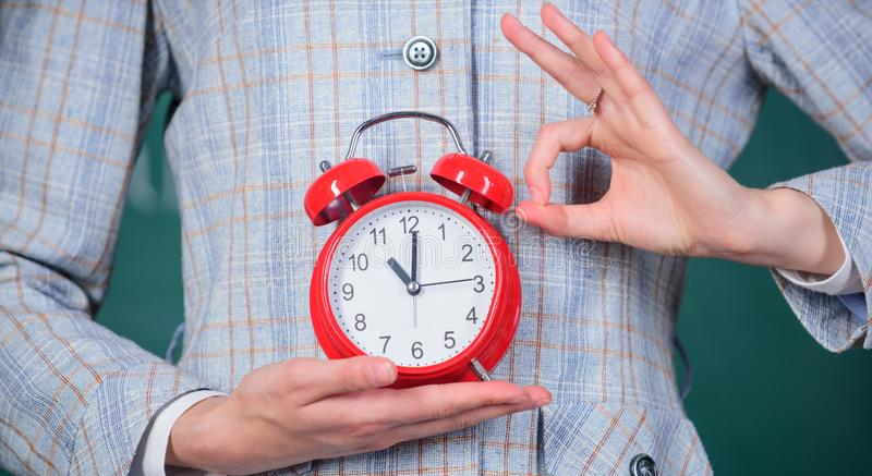 La sveglia in mani femminili si chiude su Attributi degli insegnanti Sveglia in mani dell'aula dell'educatore o dell'insegnante immagine stock