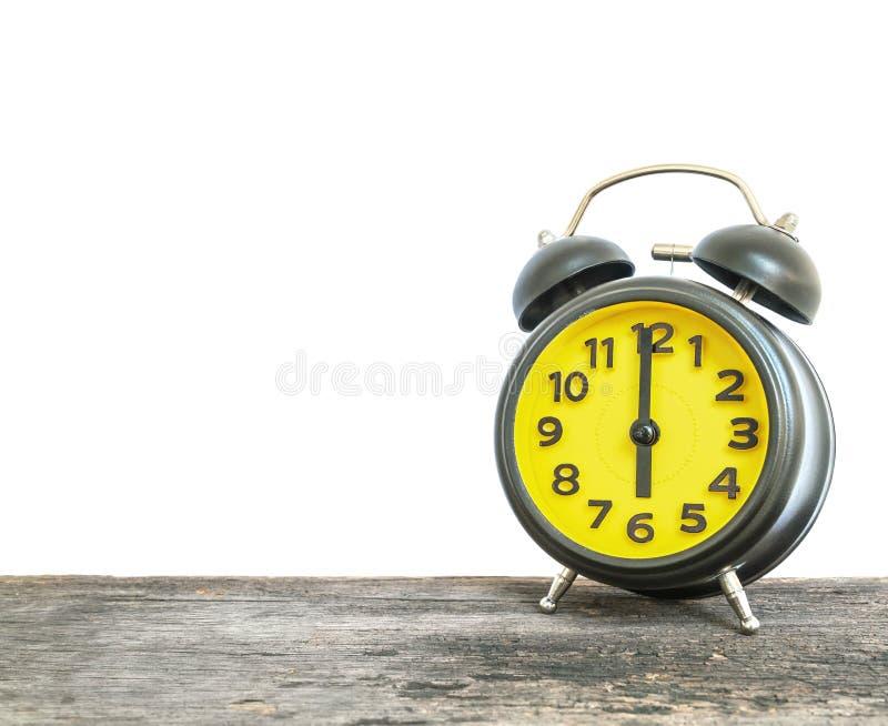 La sveglia nera e gialla del primo piano per decora in orologio del ` di 6 o sul vecchio scrittorio di legno marrone su fondo bia immagini stock libere da diritti