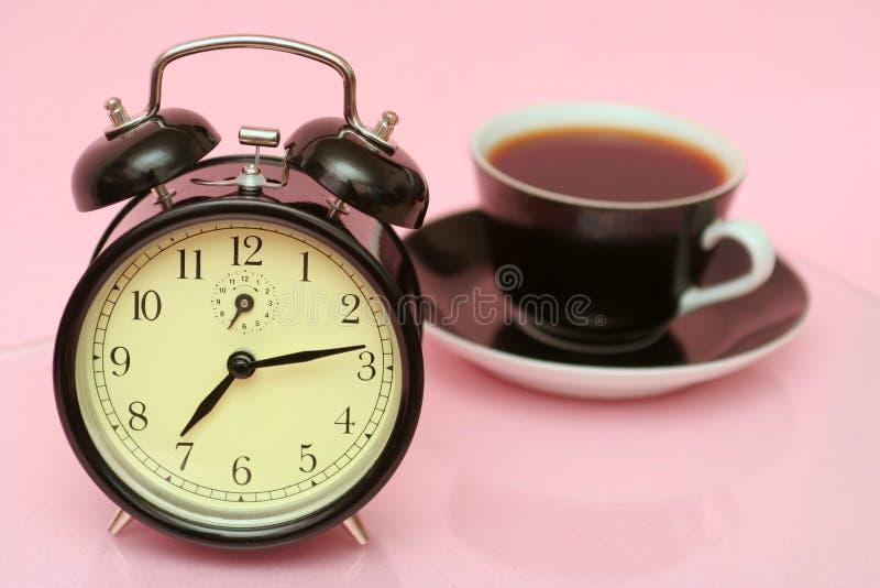 La sveglia nera e la tazza nera da caffè fotografia stock