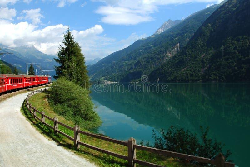 La Svizzera: Luglio 2012, il treno svizzero Bernina della montagna esprime nel lago di Poschiavo fotografia stock libera da diritti