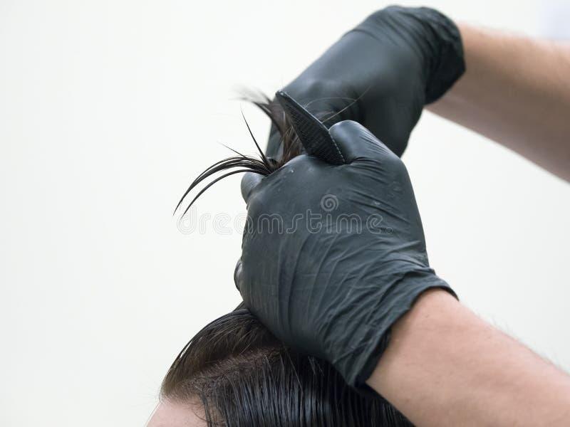La técnica de cortar con el pelo largo de las tijeras foto de archivo