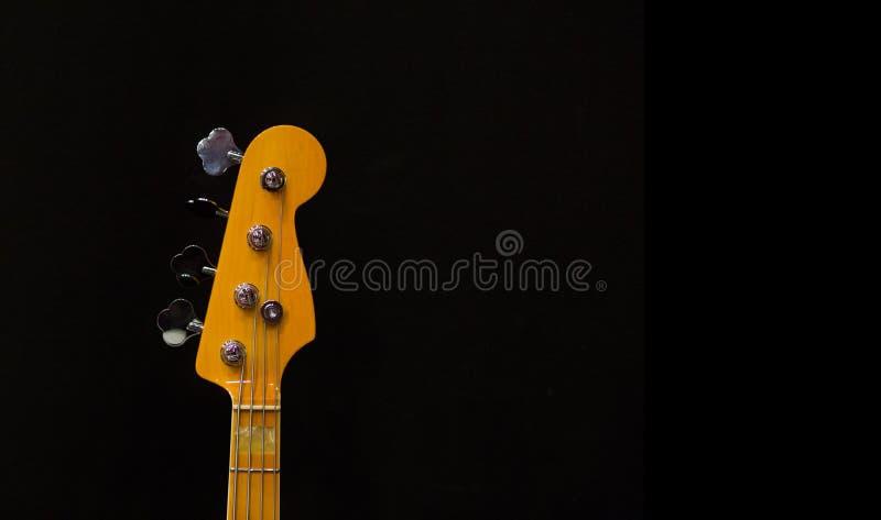 La tête d'un cou de guitare sur un fond noir image libre de droits