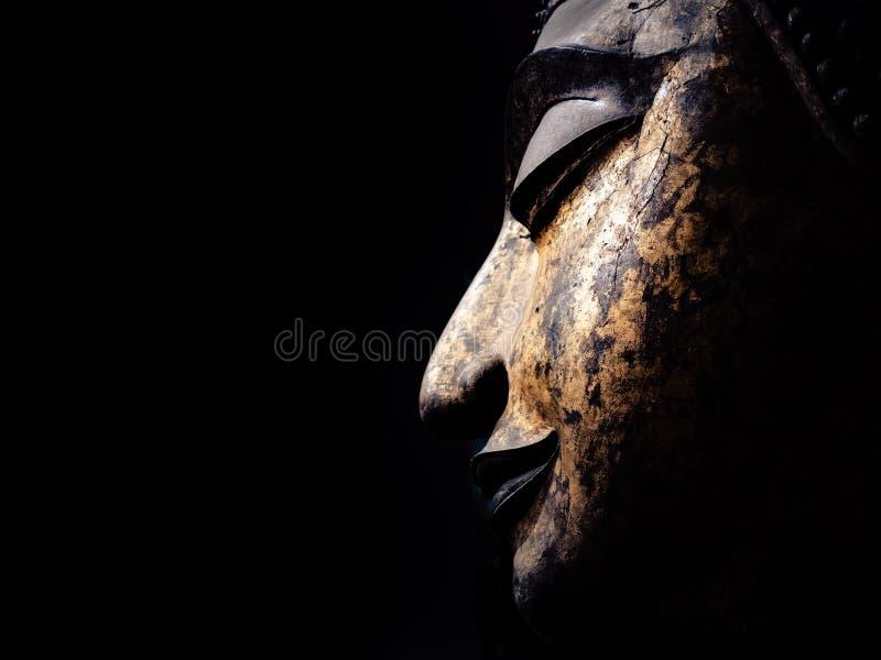 La tête d'une image antique de Bouddha sur le fond noir images libres de droits