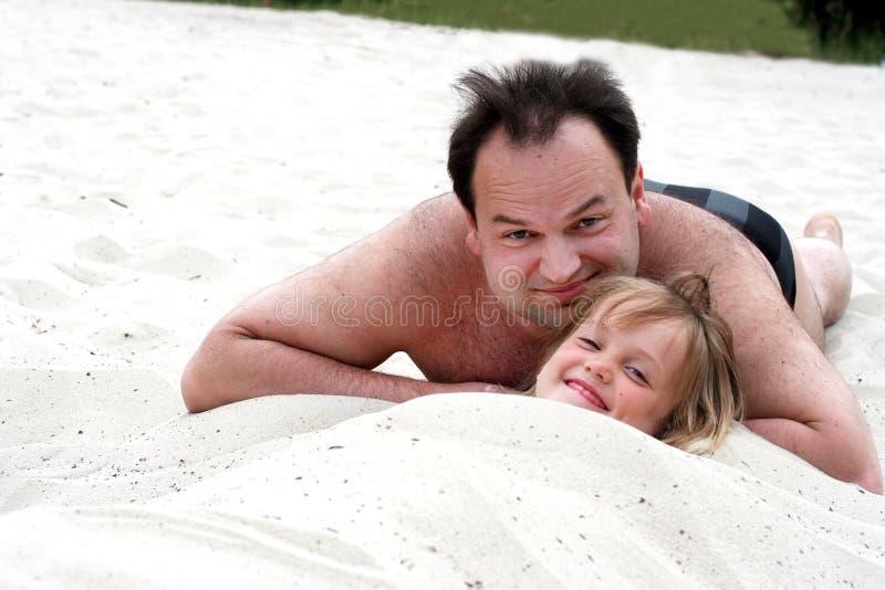 la tête d'une petite fille drôle collant hors du sable avec un homme de sourire se trouvant près de elle dans la plage photo libre de droits