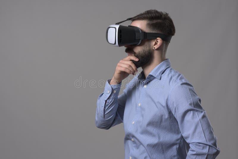 La tête de port de jeune homme d'affaires occasionnel futé adulte a monté le casque de vr regardant loin le copyspace et la pensé photo stock