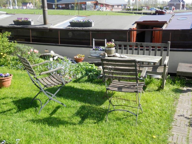 La Tabella e le sedie sul canale parteggiano in paesino di pescatori olandese immagine stock libera da diritti