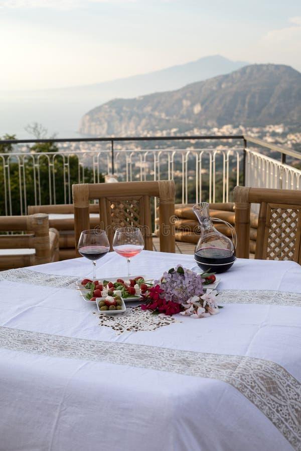 La Tabella sul terrazzo ha preparato per una cena romantica che trascura il golfo di Napoli e del Vesuvio fotografia stock libera da diritti