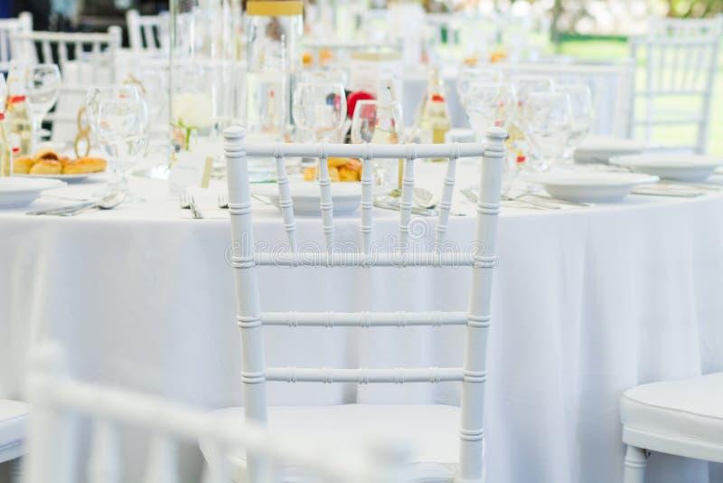 La tabla blanca de la silla y de la suposición fijó para una cena de boda imagen de archivo