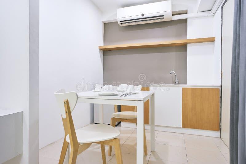 La tabla blanca fijó con las sillas de madera, concepto moderno de la cocina para el interior del apartamento foto de archivo