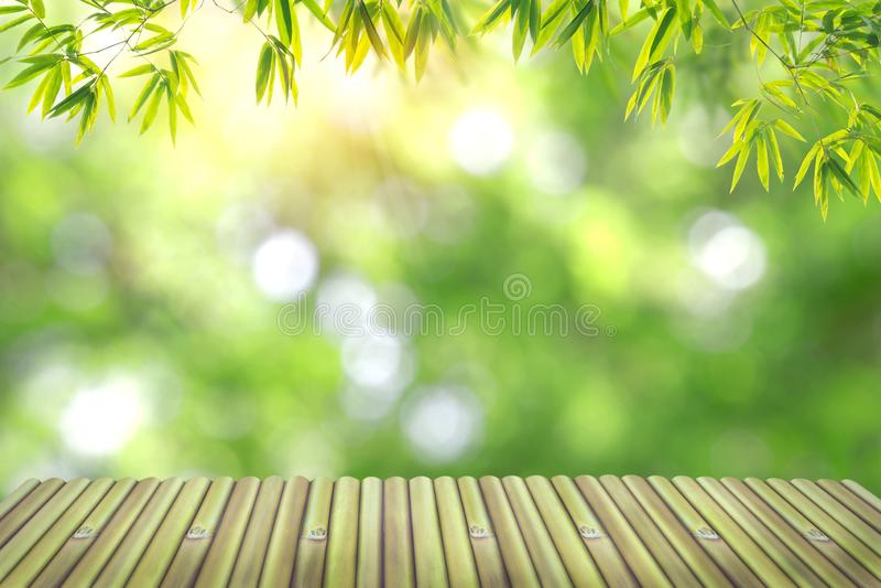 La tabla de bambú vacía en fondo el top tiene una luz natural del bokeh foto de archivo libre de regalías