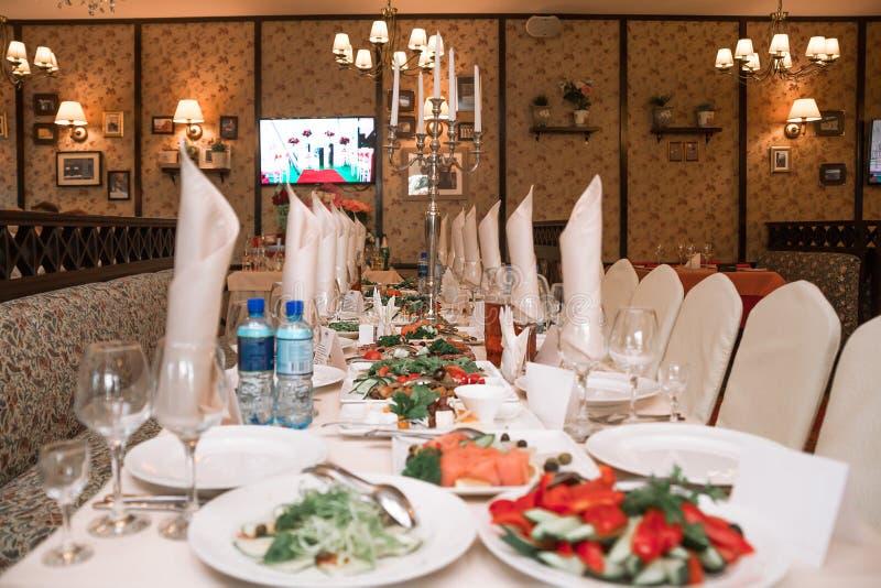 La tabla de banquete en el restaurante es completamente reservada y los bocados están en la exhibición imágenes de archivo libres de regalías