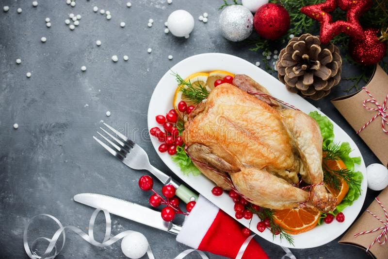 La tabla de cena temática de la Navidad asó el pollo y el deco de la Navidad fotografía de archivo