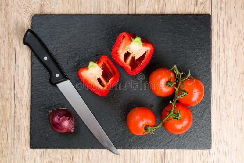 La tabla de cortar negra con el cuchillo y las verduras, alista para cortar fotografía de archivo