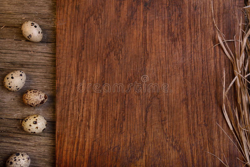 La tabla de cortar rústica de madera vacía con los huevos de codornices copia el espacio para el texto foto de archivo libre de regalías