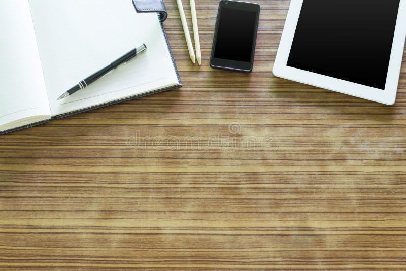 La tabla de la oficina con la tableta, pluma en el cuaderno, smartphone en viejo corteja fotografía de archivo libre de regalías