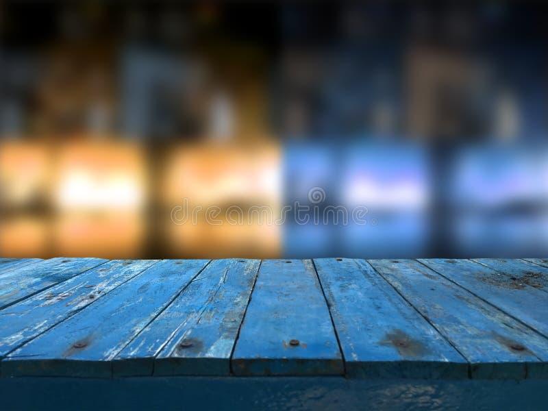 La tabla de madera azul marino vacía delante del extracto empañó el fondo de la falta de definición del restaurante Puede ser uti foto de archivo