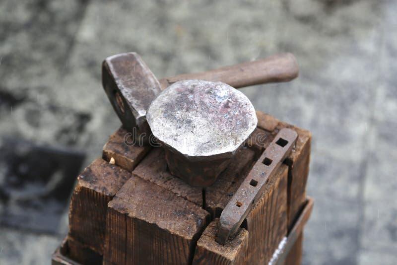 La tabla de madera de barras de un árbol es sujetada por un soporte grande y un yunque a un martillo para los asuntos de la fragu imágenes de archivo libres de regalías