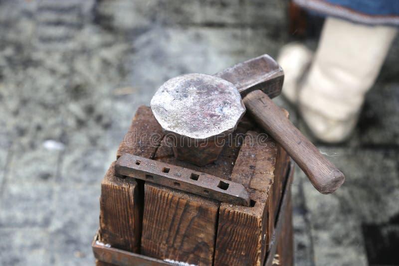La tabla de madera de barras de un árbol es sujetada por un soporte grande y un yunque a un martillo para los asuntos de la fragu fotografía de archivo libre de regalías
