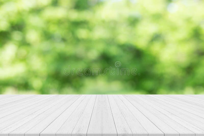 La tabla de madera blanca vacía con verde de la naturaleza empañó el fondo fotografía de archivo